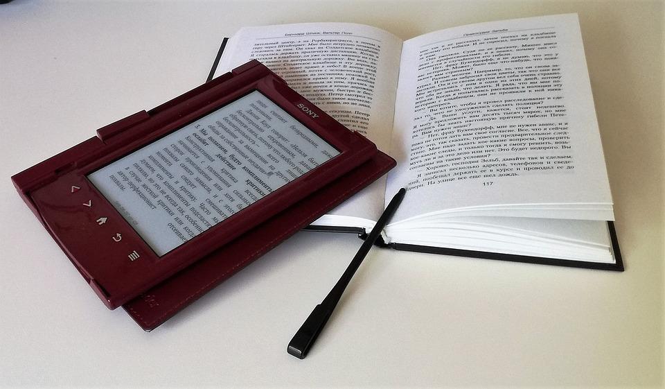 Sony e-reader next to open book
