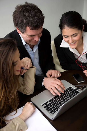 Three business people reviewing something on a computer screen