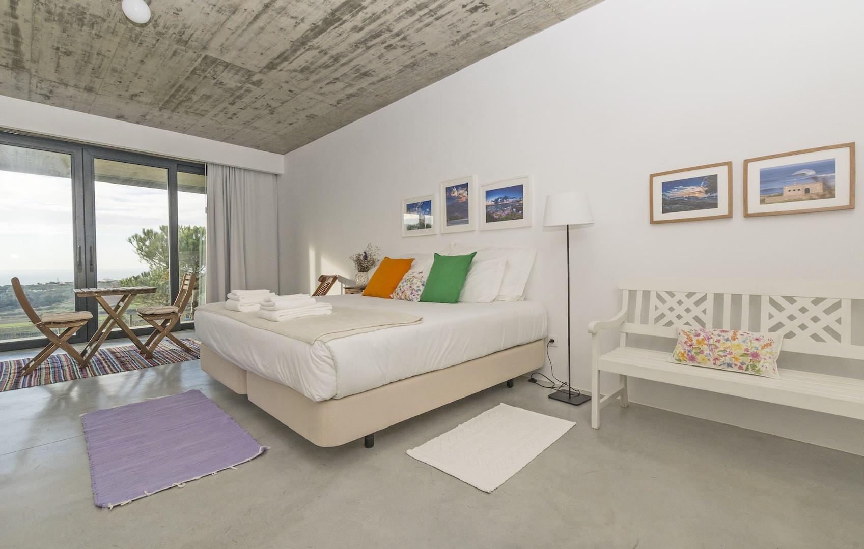 Esta imagem descreve um quarto dentro da Quinta Raposeiros. Este quarto tem uma cama no meio e uma muito boa decoração
