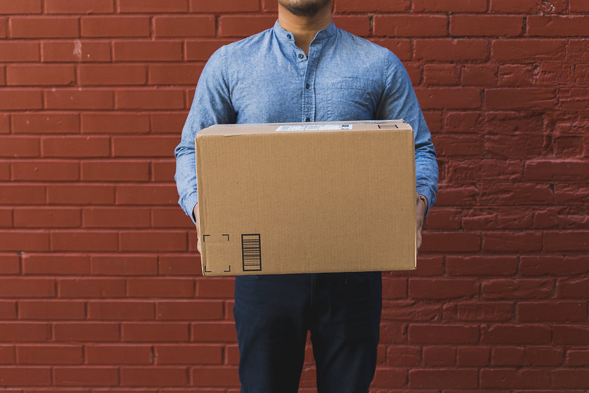 man-holding-shipping-box-on-red-brick.jp