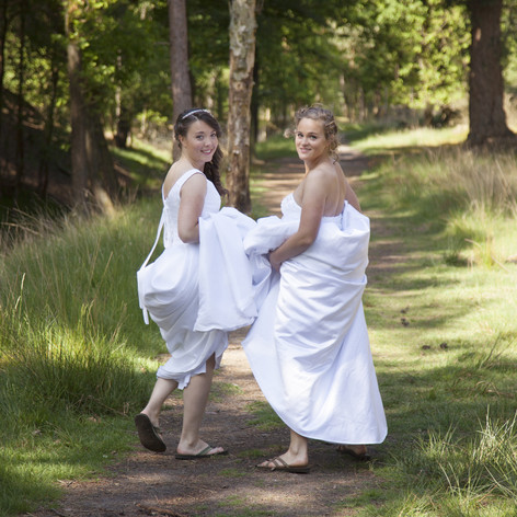 two brides walk on forest path with skir