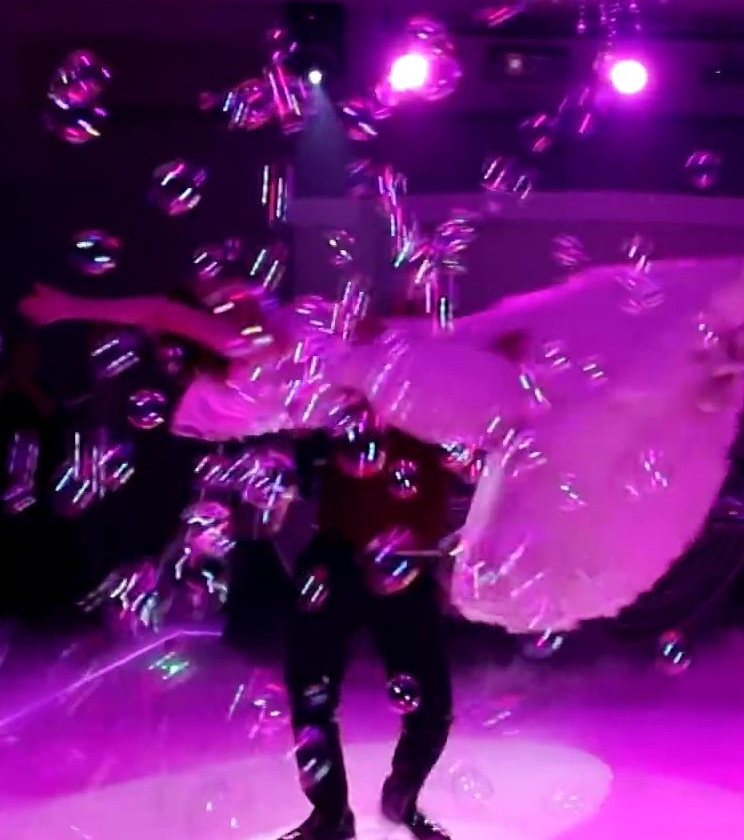 Wedding dance couple performing a lift in bubbles