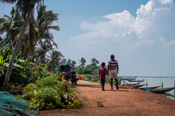 A father walking with his son along the shore of Bherapura Island.