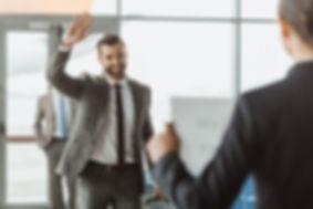 businessman waving to partner who waitin