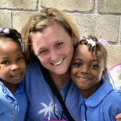 Chareyl Moyes of Washington Terrace, co-founder and executive director of the Haitian Roots nonprofit, with two Haitian children. The organization operates two schools in Haiti and plans a third.