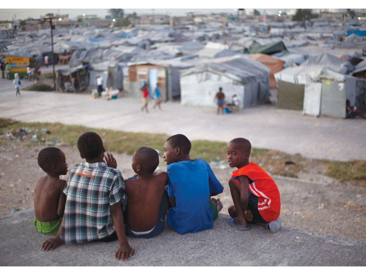 A group of boys sit on the rooftop of a home damaged by the 2010 earthquake, across from the Jean Marie Vincent camp where they now reside, in Port-au-Prince, Haiti. There are nearly 360,000 people still living in the encampments that sprouted throughout the city after the earthquake.  DIEU NALIO CHERY, The Associated Press