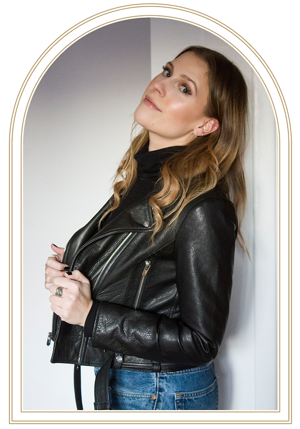Portrait of Jen leaning against white wall while wearing a leather jacket.