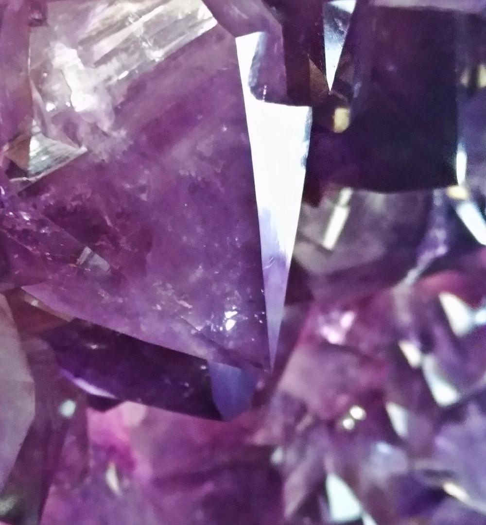 Quando começamos a nos interessar por cristais, um dos primeiros que chegam até nós é a ametista. Encontrado fartamente do Brasil, sua cor varia desde um lilás transparente e claro, à roxo intenso, lembrando tons de uva.
