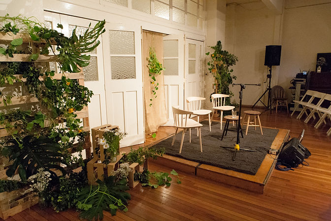 photo of empty stage set with plants and flowers