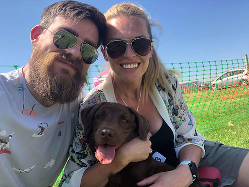 Bearded man with his arm around a lady and a dog sitting in the grass
