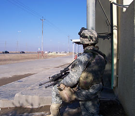Specialist Ryan A. Conklin pulling security on the streets of Tikrit, Iraq 2005