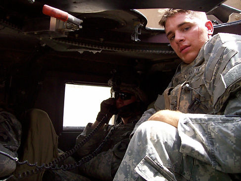 Specialist Ryan A. Conklin in turret of Army Humvee on patrol in Tikrit, Iraq