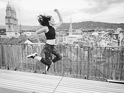 sporty woman jumping on a rooftop with a view on the city of zürich