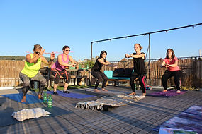 women doing squat exercises on a sunny rooftop