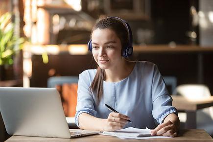 Focused woman wearing headphones using l