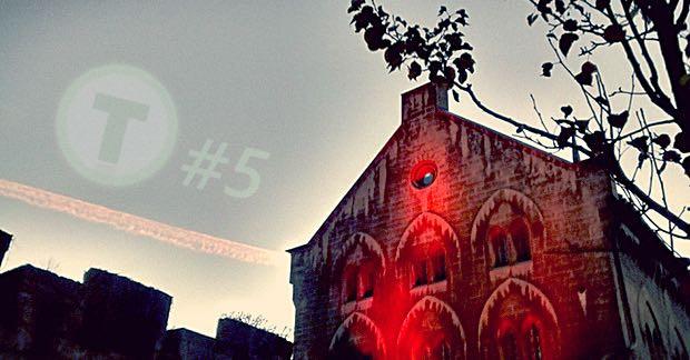 Rot beleuchtetes Fabrikgebäude und in dem Himmel ist das Tad Time Logo und der Zusatz #5 zu sehen