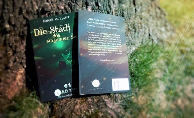 Gewinnspiel Fantasyroman Tad Time: 2 Bücher lehnen an Baum, der mit Sternenglitzer umgeben ist