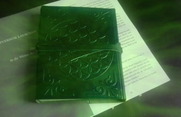 Grünes magisches Buch auf Schreibtisch