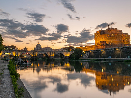 The view of Rome at sunset with two of its most iconic monuments: the Papal Basilica of Saint Peter in the Vatican and Castel Sant'Angelo.