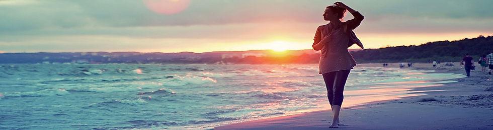 Donna che cammina lungo la spiagga