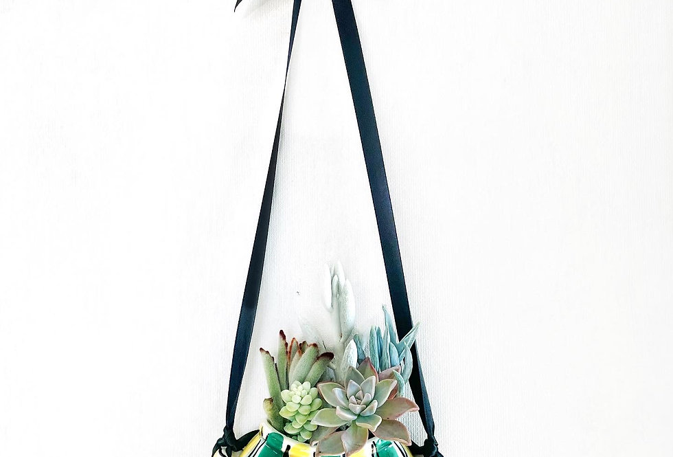 A beautiful vintage German hanging vase filled with a variety of succulents