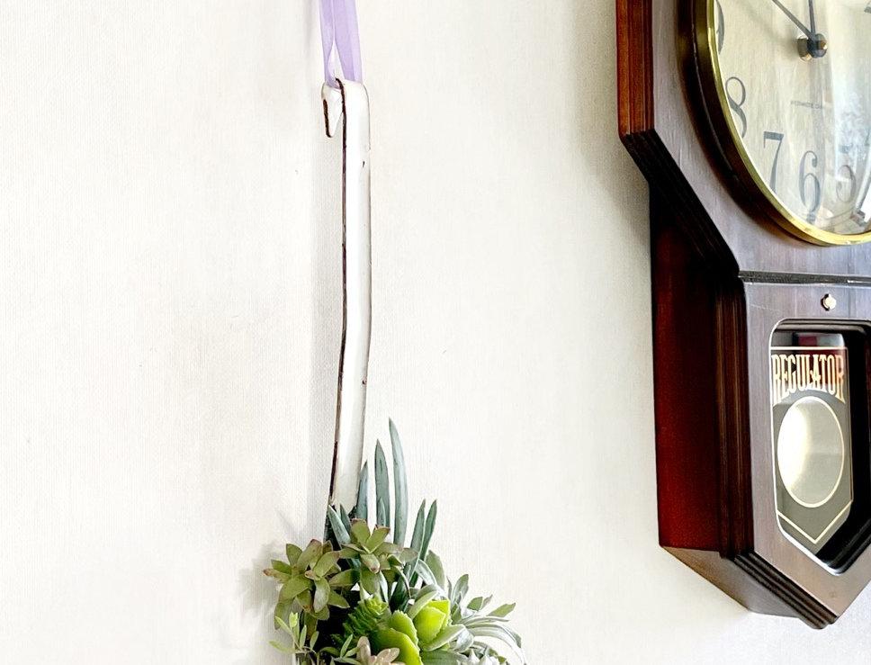 A large vintage enamel ladle filled with succulents