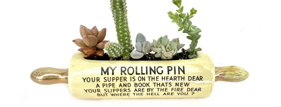 Cute as vintage rolling pin vase filled with colourful succulents