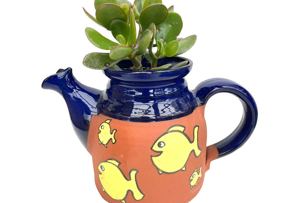 A large teapot with fish design home to a Jade plant succulent