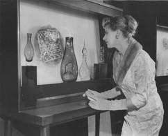 Woman views glass sculptures in exhibit
