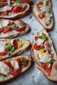 Bruschetta de pão italiano com tomate cereja pimentão presunto de parma ervas finas e manjericão