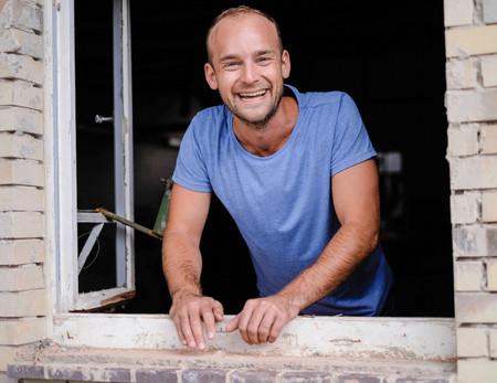 Felix Schlebusch steht lachend in offenem Fenster auf stillgelegter Industrieanlage in Giessen