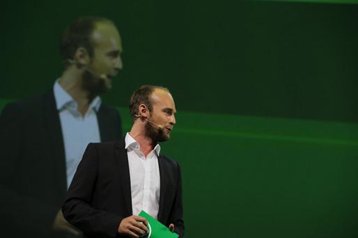Felix Schlebusch mit Moderationskarten in der Hand und Blick ins Publikum und Projektion des Kamerabilds auf die Leinwand hinter ihm. Foto ©Commotion GmbH