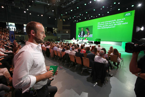 Felix Schlebusch in Erwartung der Schaltung zur Hauptbühne bei der Moderation einer Tagung für einen Krankenversicherer. Foto ©Commotion GmbH