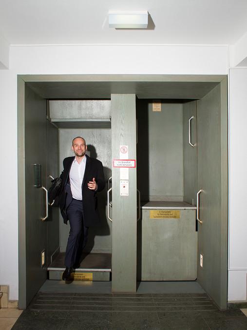 Felix Schlebusch springt freudig, lachend aus dem Paternoster im Deutschlandhaus in Essen.