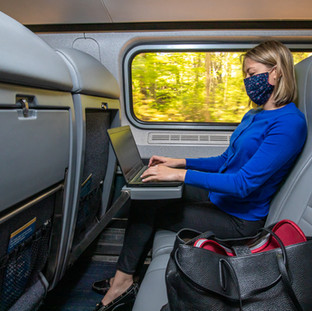 Business lady at seat with mask on lapto