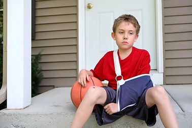 Boy with arm in a sling receiving urgent care from Brown Emergency Medicine TeleCare.