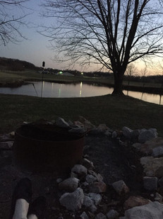 View of the back of the facility. The pond and campfire