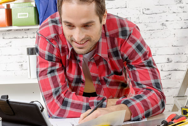 a smilling young man using the tablet fo