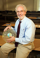 A teacher with a world map sphere on his hand