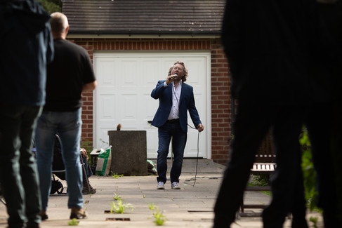 A man sings on his driveway for his neighbours in Wigan.