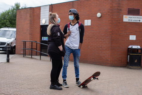 A masked couple talk outside Wigan North Western station.
