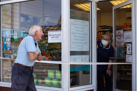 A customer and pharmacist talk from a social distance at Standish Pharmacy, Standish.