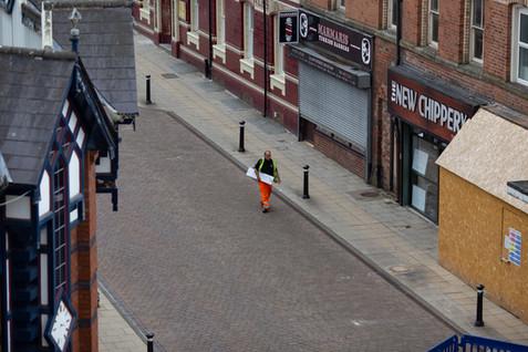 A builder walks down an empty Wigan high street during lockdown.