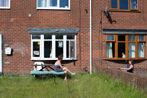 Two neighbours chat from a social distance, Wigan.