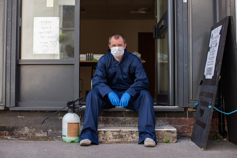 A man takes a break in work gear outside 'Covid-19 Buster' pop up community shop, Leigh.