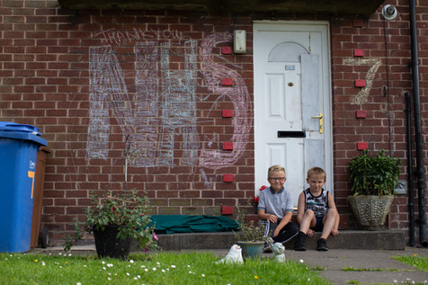 Two boys sit next to NHS lettering outside their house, Chorley.