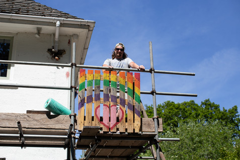 A roofer poses next to his rainbow  pallet, Chorley.