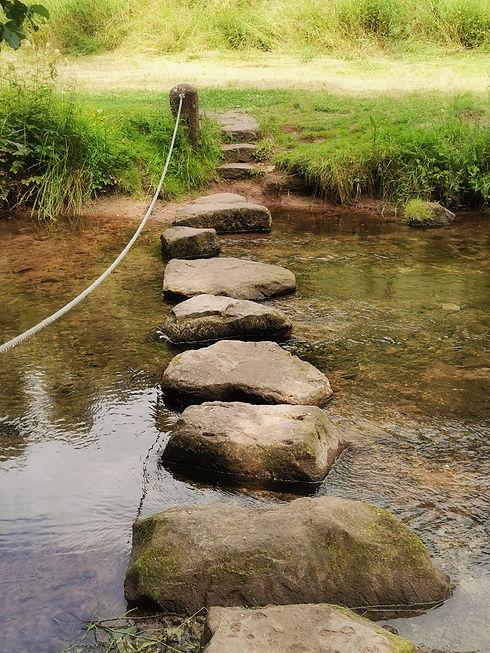 Einzelberatung Life-Coaching ein Fluss mit großen Steinen und einem Seil zum Überschreiten