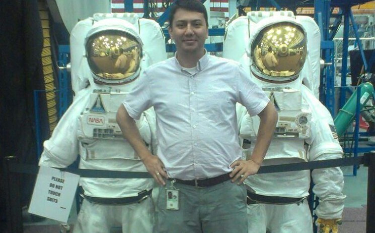 Serkan Golge pictured in front of Nasa spacesuits