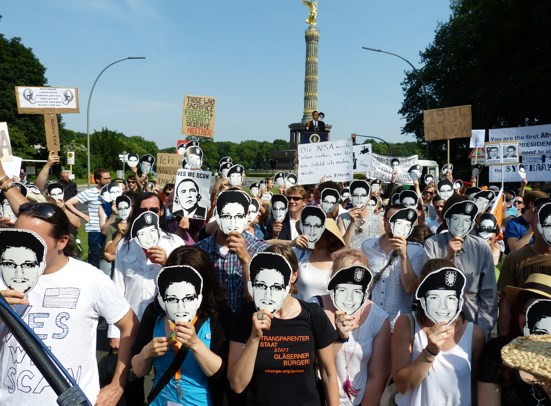 Protesters against PRISM in Berlin, Germany wearing Chelsea Manning and Edward Snowden masks (June 19, 2013). Photo source: Wikimedia commons.